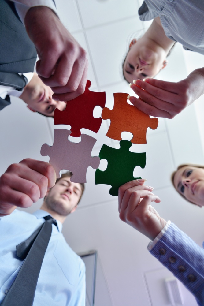Group of business people assembling jigsaw puzzle and represent team support and help concept.jpeg
