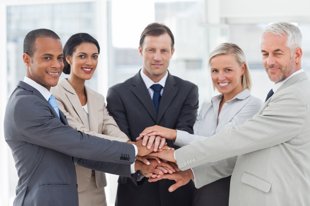 Group of business people piling up their hands together in the workplace.jpeg