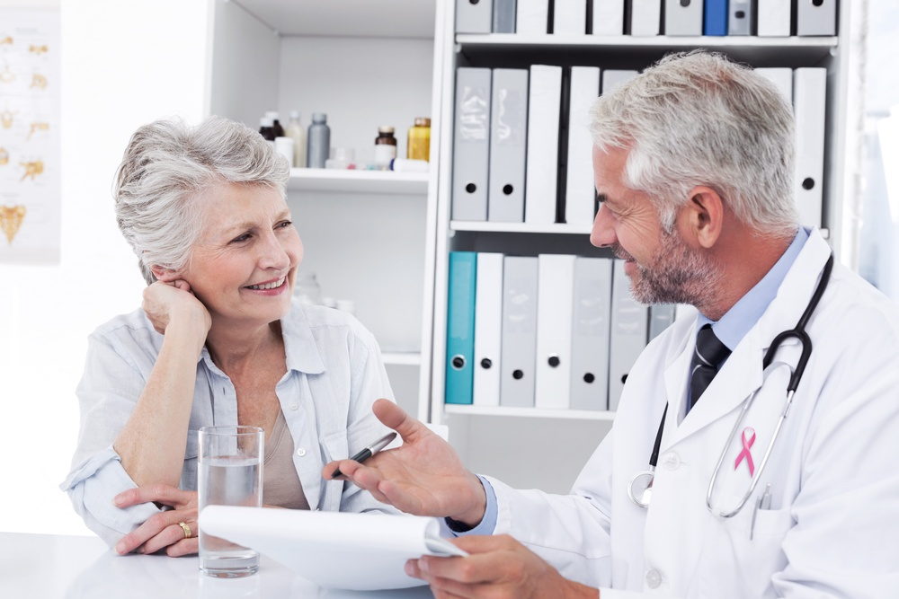Pink awareness ribbon against female senior patient visiting a doctor.jpeg