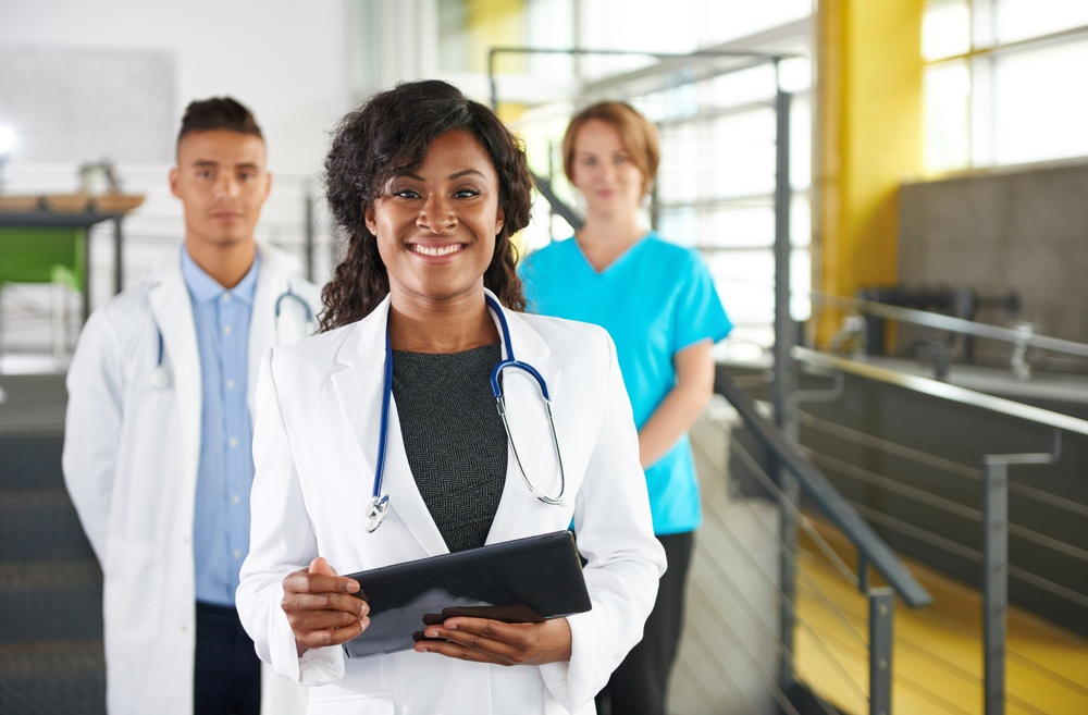 Portrait of a friendly female african american doctor and team in bright modern office.jpeg