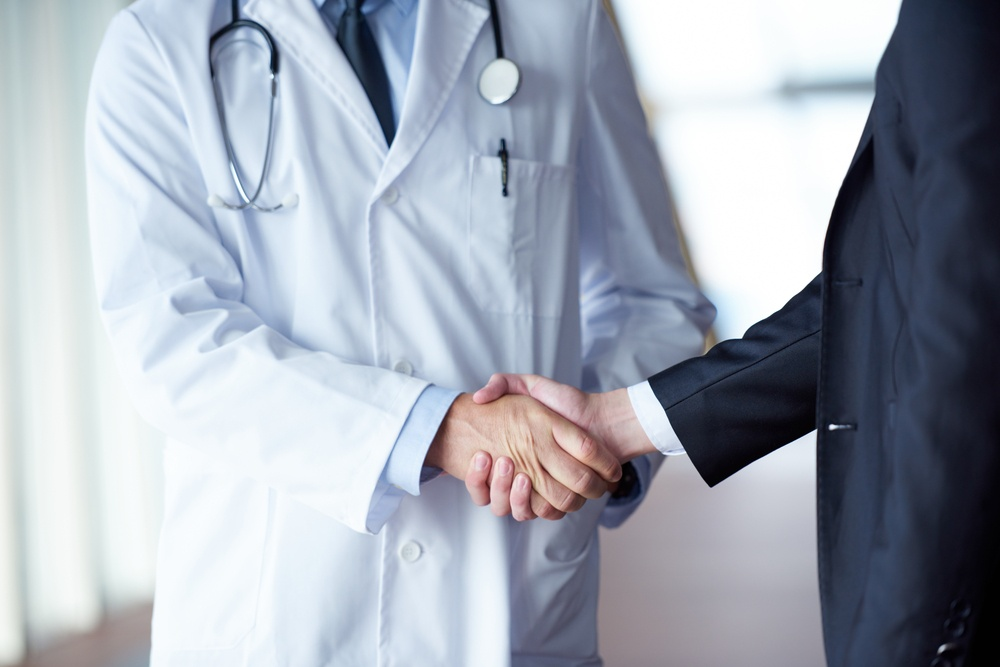 doctor handshake with a patient at doctors bright modern office in hospital-1.jpeg