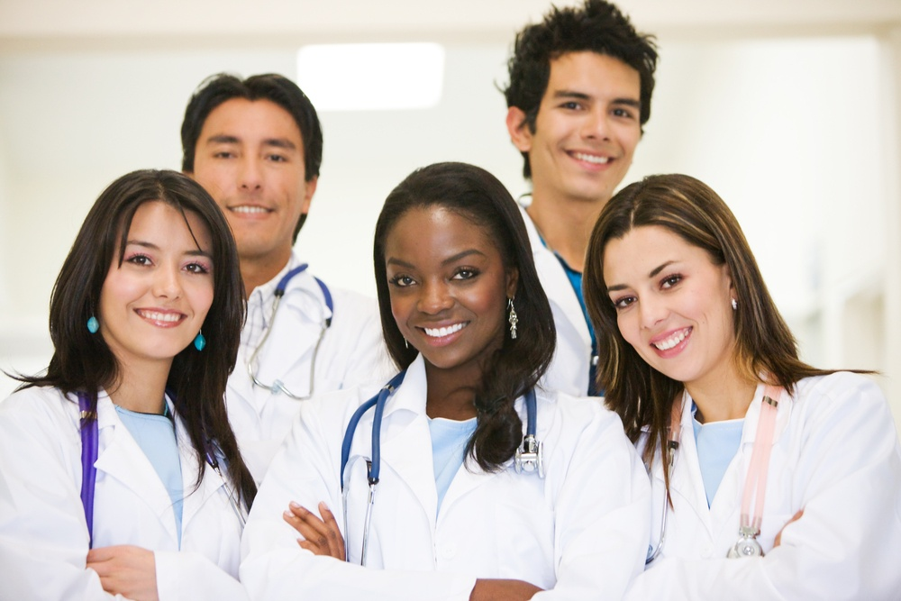 group of doctors standing and smiling in a hospital.jpeg